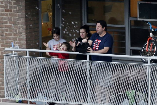A family cheers, makes noise and blows bubbles from their balcony to salute the healthcare workers in New York City on April 14. Photo by John Angelillo/UPI