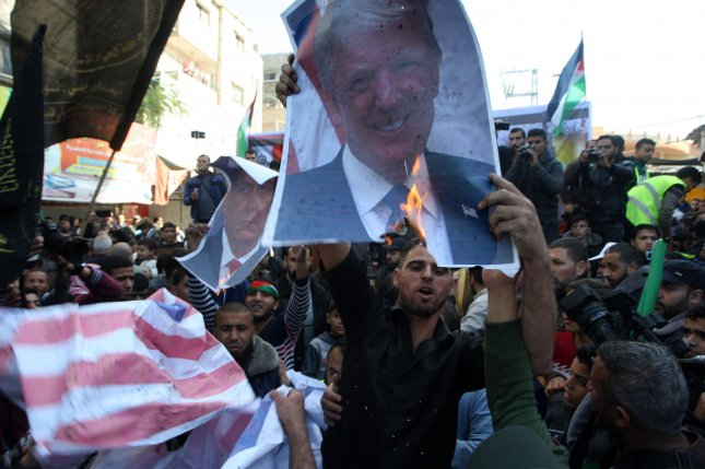 Palestinians burn portraits of U.S. President Donald Trump during a protest in the southern Gaza Strip town of Rafah on December 8, 2017. Photo by Ismael Mohamad/ UPI