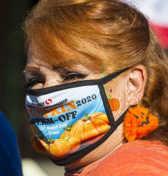 A masked woman is seen during the 47th annual Championship Pumpkin Weigh-off in Half Moon Bay, Calif., on Monday. Photo by Terry Schmitt/UPI