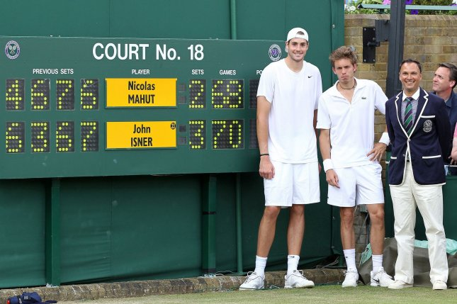 A victorious John Isner (L) and Nicolas Mahut (R) stand in front of the scoreboard after Isner won the longest tennis match in history in the final set 70-68 in the Wimbledon championships on June 24, 2010. File Photo by Hugo Philpott/UPI