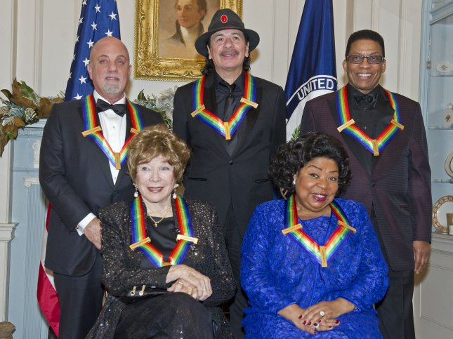 The five recipients of the 2013 Kennedy Center Honors pose for a photo following a dinner hosted by United States Secretary of State John F. Kerry at the U.S. Department of State in Washington, D.C. on December 7, 2013. Seated in the front row, from left, are: Shirley MacLain, and Martina Arroyo. Standing, from left, are Billy Joel, Carlos Santana, and Herbie Hancock. The 2013 honorees are opera singer Martina Arroyo; pianist, keyboardist, bandleader and composer Herbie Hancock; pianist, singer and songwriter Billy Joel; actress Shirley MacLaine; and musician and songwriter Carlos Santana. UPI/Ron Sachs/Pool