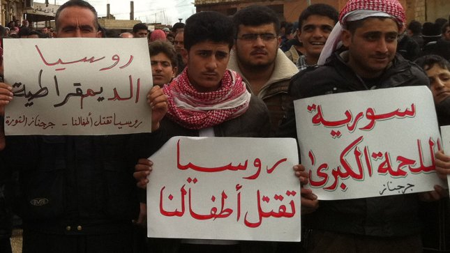 Syrian protesters hold banners that read in Arabic (Russia kills our children) during a protest against Syria's President Bashar al-Assad in Jrbanaz near Idlib in Syria on February 11, 2012. UPI