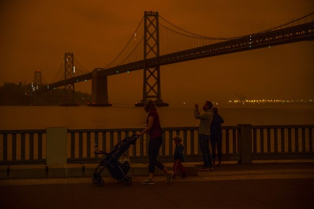 A mixture of fog and smoke casts an orange glow around the Bay Bridge on Wednesday morning, as seen from the Embarcadero in San Francisco, Calif. Photo by Terry Schmitt/UPI
