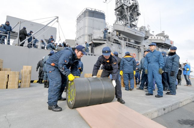 Members of Japan Ground and Maritime Self-Defense Force unload drum of fuel from destroyer (DE-233) Chikuma as they aid in the massive earthquake and tsunami that devastated the country, in Kamaishi, Iwate prefecture, Japan, on March 17, 2011. UPI/Keizo Mori
