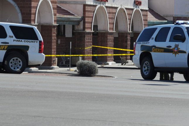Sheriff's deputies' vehicles are parked near an entrance to a Tucson shopping mall where a gunman's attack Jan. 8, 2011, left six people dead and 13 wounded, including U.S. Rep. Gabrielle Giffords. UPI/Art Foxall/File