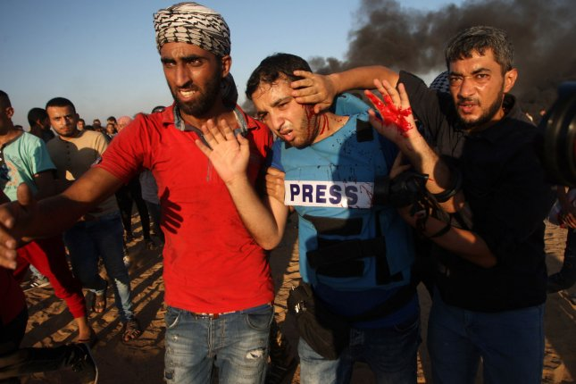 Palestinian protestors evacuate injured journalist Mahmoud Bassam during a demonstration at the Israel-Gaza border in Rafah in the southern Gaza Strip on Friday. Photo by Ismael Mohamad/UPI