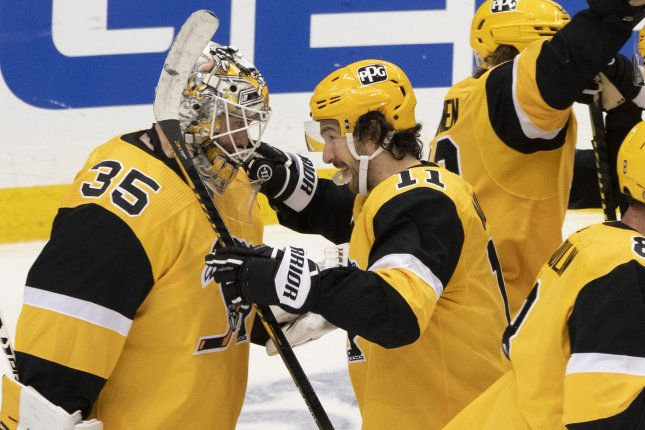 Pittsburgh Penguins goaltender Tristan Jarry (35) and center Frederick Gaudreau (11) celebrate following their 2-1 win against the New York Islanders in the first round of the NHL Stanley Cup Playoffs series Tuesday at PPG Paints Arena in Pittsburgh. Photo by Archie Carpenter/UPI