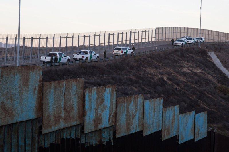 U.S. Border Patrol agents watch migrants cross into San Ysidro, Calif., on December 2. Photo by Ariana Drehsler/UPI