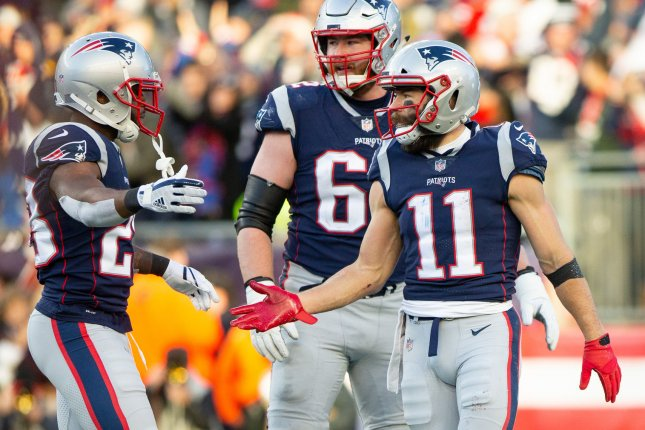 New England Patriots running back James White (28) gives a high five to wide receiver Julian Edelman (11) after Edelman scored on a 32-yard reception in the third quarter against the Buffalo Bills on December 23 at Gillette Stadium in Foxborough, Mass. Photo by Matthew Healey/UPI
