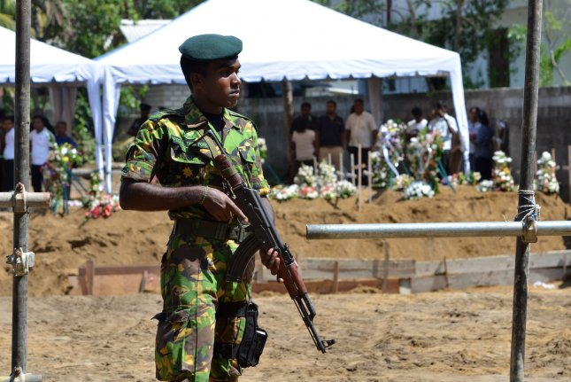 An armed security guard patrols the area during victims' funerals Tuesday. Photo by Perera Sameera/UPI