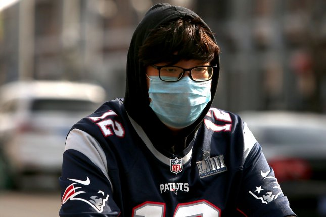 A Chinese man wearing a Tom Brady jersey wears a protective face mask despite reports of a decline in the threat of the Covid-19 virus in Beijing on Tuesday. Photo by Stephen Shaver/UPI