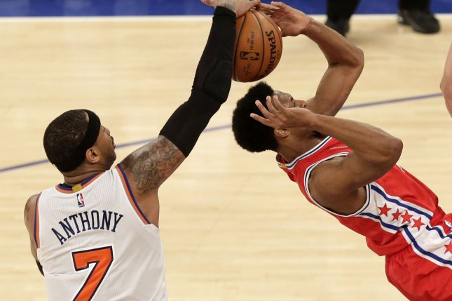 New York Knicks' Carmelo Anthony blocks a shot from Philadelphia 76ers' Ish Smith in the first overtime period at Madison Square Garden in New York City on January 18, 2016. The Knicks defeated the 76ers 119-113 in double overtime. Photo by John Angelillo/UPI