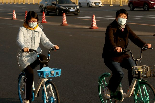 Chinese bicycle past an empty Tiananmen Square wearing protective masks due to the coronavirus alert in Beijing on Wednesday, January 29, 2020. Photo by Stephen Shaver/UPI