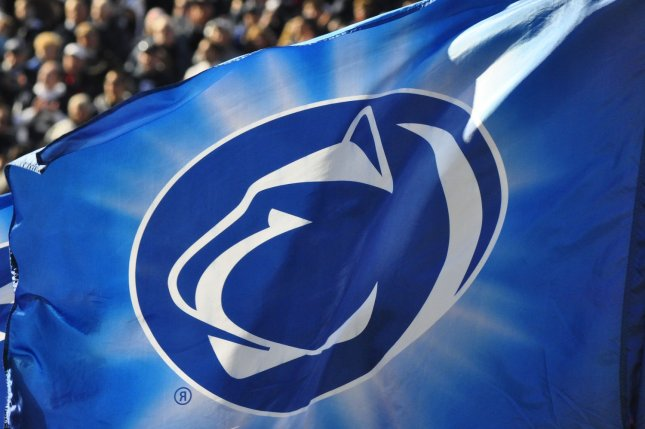 A fan waves a flag with the logo of the Penn State Nittany Lions at a football game at Beaver Stadium in State College, Penn. Monday, attorneys delivered opening remarks in a whistleblower case against the university, which claims former staffer Mike McQueary was railroaded by the school during and after the abuse investigation of assistant coach Jerry Sandusky in 2011. File Photo by Archie Carpenter/UPI