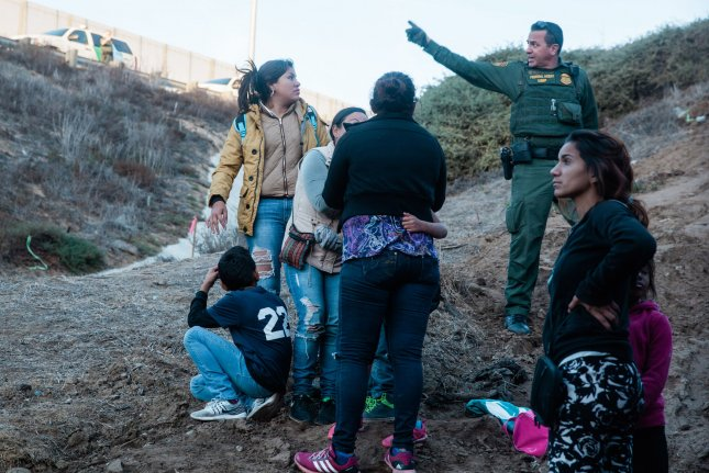 A U.S. Border Patrol agent speaks to the women and children who crossed illegally into San Ysidro, Calif., on December 2. Photo by Ariana Drehsler/UPI