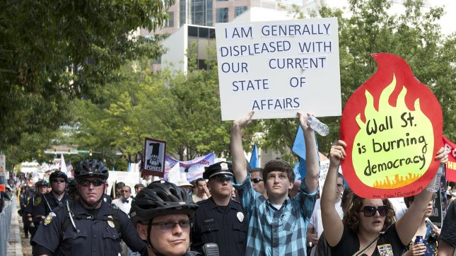 Protesters join forces while flanked by crowd control police during an Occupy rally at the 2012 Democratic National Convention in Charlotte, North Carolina on September 2, 2012. UPI/Gary C. Caskey