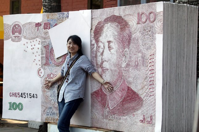 A Chinese girl stands in front of a Chinese RMB100 note, equivalent to $15, in central Beijing. North Korea is circulating counterfeit Chinese currency, experts say. File Photo by Stephen Shaver/UPI