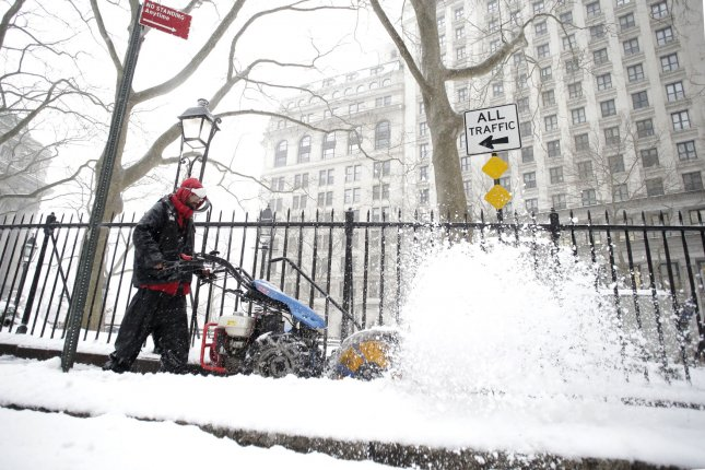 A worker clears the sidewalks with a snow blower in lower Manhattan in a snow storm in New York City on Tuesday. The storm had less of an impact on major cities across the northeast than anticipated, but some towns further inland received up to 30 inches of snow. Photo by John Angelillo/UPI