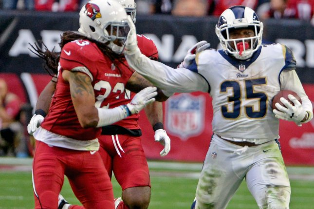 Los Angeles Rams' C.J. Anderson (R) gives Arizona Cardinals' Tre Boston a stiff arm as he picks up a first down in the fourth quarter of the game on Sunday at State Farm Stadium in Glendale, Ariz. Photo by Art Foxall/UPI