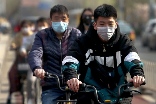 Bicyclists wear face masks in Beijing, China, on Thursday. Worldwide, there have so far been nearly 200,000 deaths since the coronavirus outbreak began and more than 2.7 million cases. Photo by Stephen Shaver/UPI