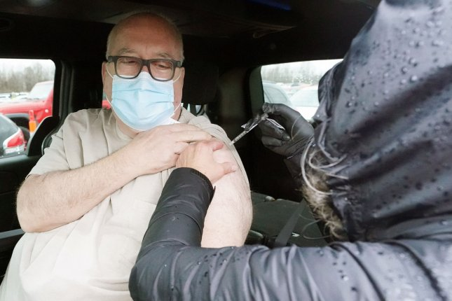 David Whitnah of Lake St. Louis, Missouri receives his first vaccination shot in his car at the Family Arena during a mass vaccination drive-in event in St. Charles, Missouri Thursday. Photo by Bill Greenblatt/UPI
