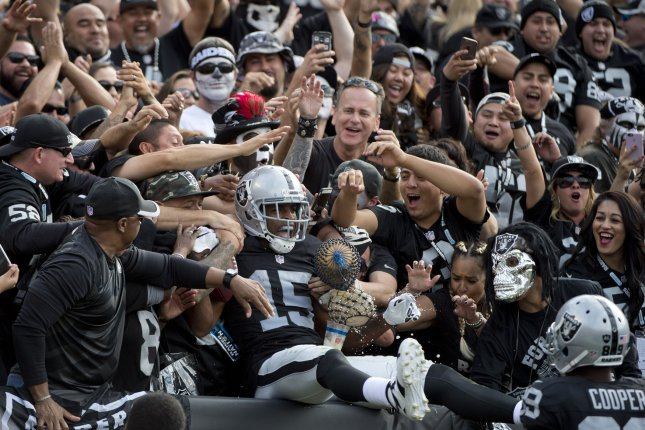 Oakland Raiders Michael Crabtree (15) leaps into the stands after a 36 yard touchdown on a pass from QB Derek Carr in the second quarter against the New York Jets at O.co Coliseum in Oakland, California on November 1, 2015. The Raiders defeated the Jets 34-20. Photo by Terry Schmitt/UPI