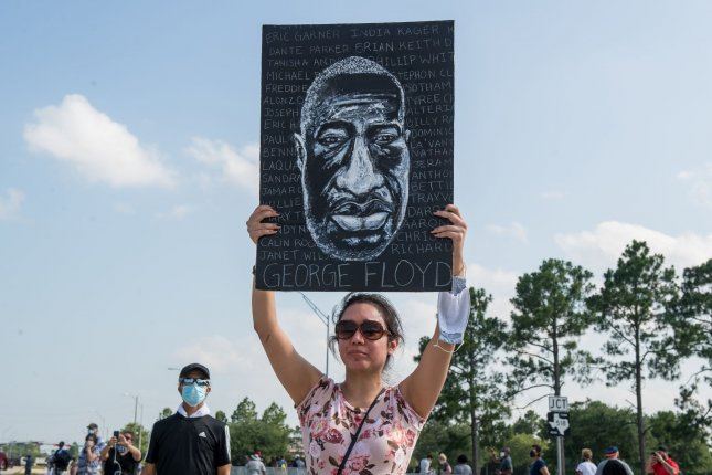 A mourner holds an image of George Floyd during his funeral at the Houston Memorial Gardens Cemetery in Pearland, Texas, on June 9, 2020. File Photo by Trask Smith/UPI