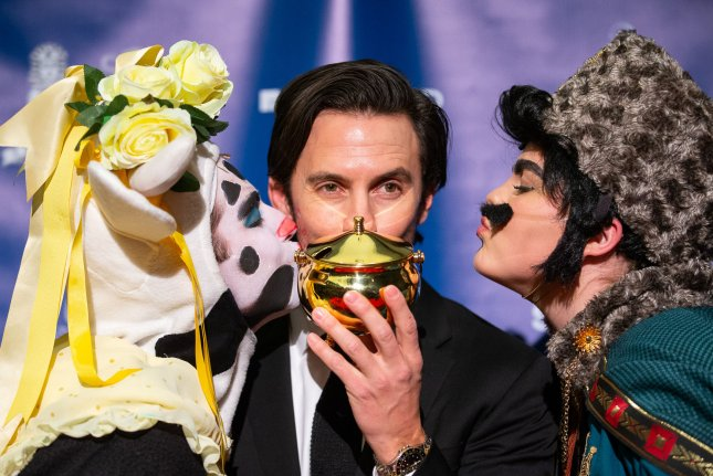 Actor Milo Ventimiglia, pictured here flanked by Hasty Pudding Theatricals cast members, kisses his Pudding Pot trophy after he was honored as the Harvard University troupe's 2019 Man of the Year in Cambridge, Massachusetts on Friday. Photo by Matthew Healey/UPI