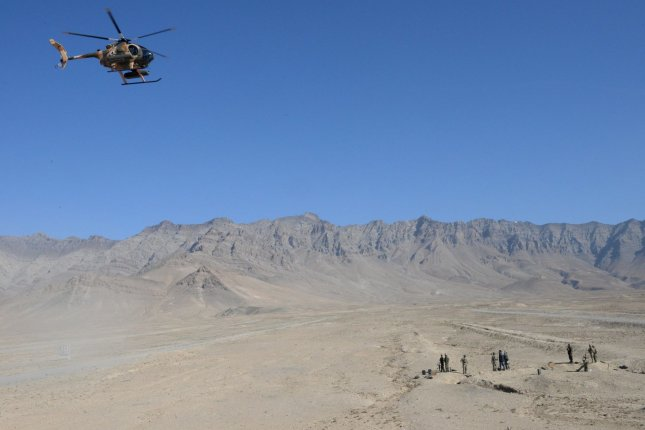An Afghan Air Force MD-530 helicopter flies over Afghan National Defense and Security Forces members during an air-to-ground integration exercise in Kabul Province, Afghanistan, in 2016. File Photo by Kay M. Nissen/NATO