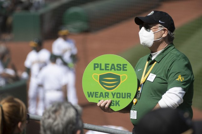 An usher holds a sign reminding fans to be masked as the Oakland Athletics take on the Houston Astros on April 3, 2021, at Oakland Coliseum in Oakland, Calif. The Minnesota Twins were scheduled to play the A's on Monday. Photo by Terry Schmitt/UPI