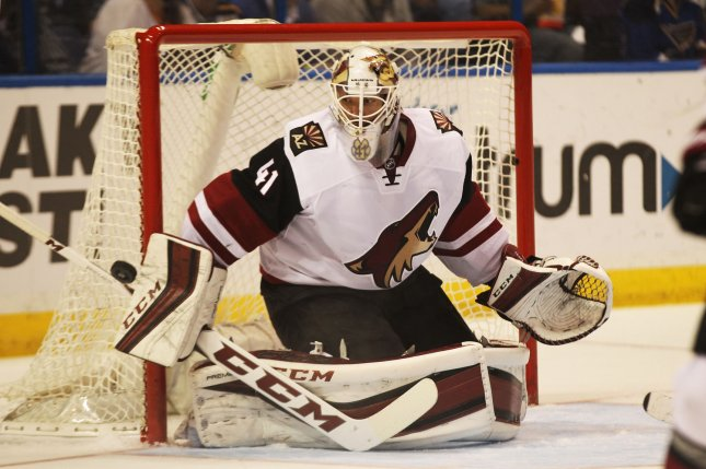 Arizona Coyotes goaltender Mike Smith knocks away a St. Louis Blues shot on goal in the first period at the Scottrade Center in St. Louis on April 4, 2016. Photo by Bill Greenblatt/UPI