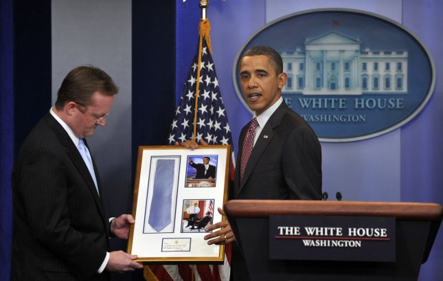 U.S. President Barack Obama returns the tie Press Secretary Robert Gibbs lent Obama for his keynote speech during the 2004 Democratic National Convention on Gibbs' last day in the Brady Press Briefing Room of the White House in Washington on February 11, 2011. Jay Carney will fill Gibbs' position. UPI/Roger L. Wollenberg