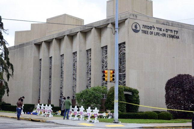 Visitors at a temporary memorial pause to reflect or lay flowers at the Tree of Life Synagogue where 11 died during a mass shooting in the Squirrel Hill neighborhood of Pittsburgh. On Wednesday, a federal grand jury indicted the alleged shooter on 44 counts. Photo by Archie Carpenter/UPI