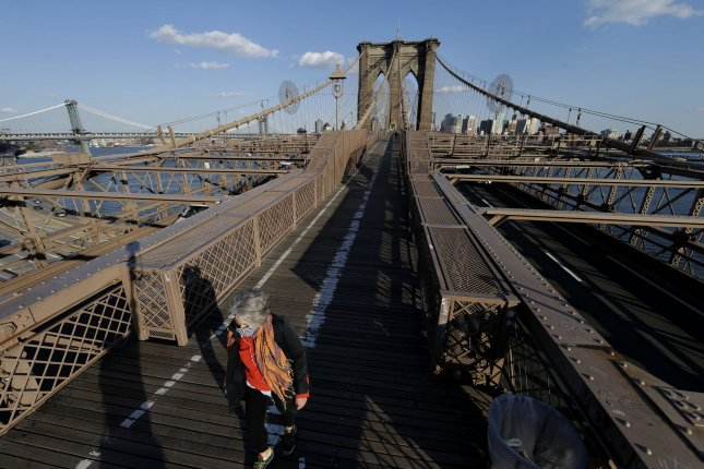 A pedestrian crosses a quiet Brooklyn Bridge in New York City on Wednesday. Mayor Bill de Blasio said at his daily briefing the city must make more than $3 billion in budget cuts due to the coronavirus crisis. Photo by John Angelillo/UPI