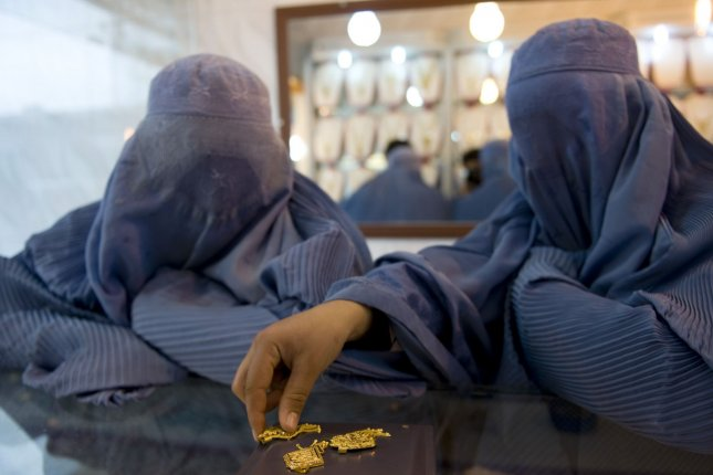 Two Afghan women wearing burkas purchase gold in a jewelry shop on February 27, 2010 in Herat, Afghanistan. UPI/Hossein Fatemi.