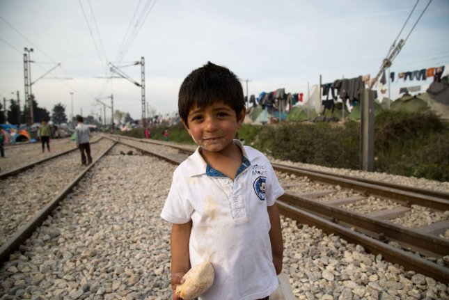 A young boy from Iraq, his face covered in flour from the loaf of bread he's been nibbling on, is pictured walking along the railroad tracks. Refugees are stranded in a makeshift camps in Greece, along the border with Macedonia, after the border was closed on March 7. Photo by David Caprara/UPI