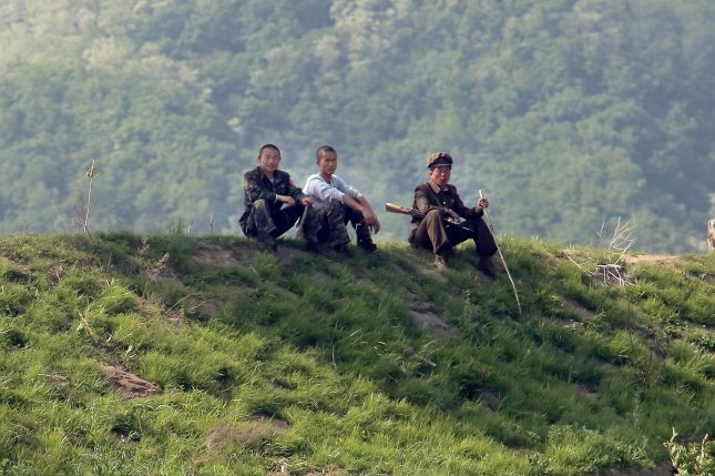 North Korean soldiers sit in the shade near the North Korean city Sinuiju, across the Yalu River from Dandong, China's largest border city with North Korea. Soldiers in the North Korean military are not provided with adequate food as Pyongyang continues to test missiles. Photo by Stephen Shaver/UPI