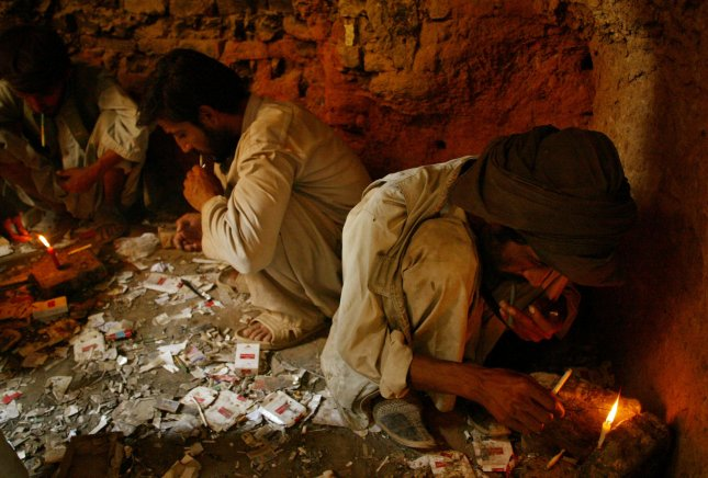 Heroin addicts smoke the drug in a part of the Old City in downtown Herat, Afghanistan on August 13, 2009. The poppy fields of Afghanistan are the source of most of the world's heroin supply and the source of the Taliban's power and money. The Afghan presidential election is on August 20. UPI/Mohammad Kheirkhah