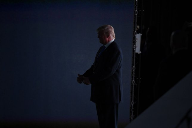 Donald Trump waits in the wings to introduce his wife Melania Trump to speak at the evening session on day one at the Republican National Convention at Quicken Loans Arena in Cleveland. Trump entered the arena to the Queen song We Are the Champions despite the band saying it was used without their permission. Photo by Pat Benic/UPI