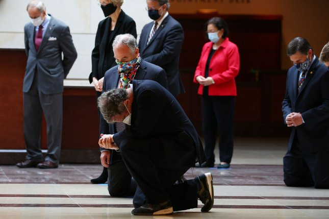 Sens. Tim Kaine and Sherrod Brown take a knee Thursday as the Senate Democratic Caucus holds 8:46 of silence to honor George Floyd, a man killed by Minneapolis police last week, in Emancipation Hall at the U.S. Capitol in Washington, D.C. Photo by Tasos Katopodis/UPI