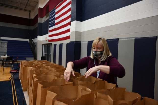 A volunteer fills bags with meals for people displaced by the winter storm at a shelter in Wylie, Texas, on Thursday. Photo by Ian Halperin/UPI