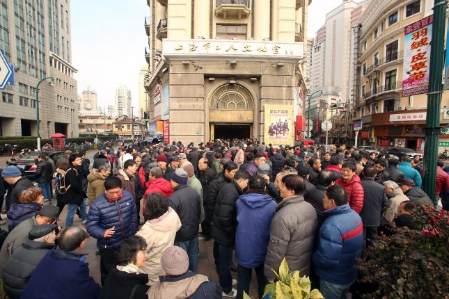 Chinese workers and pensioners in Shanghai stand outside a government office after not being paid on time on January 31, 2015. This week, the Chinese government announced it would cap Shanghai's population at 25 million to avoid strains on social services. File Photo by Stephen Shaver/UPI