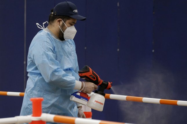 A worker sanitizes areas at a COVID-19 vaccination site in Livingston, N.J., on Monday. Photo by John Angelillo/UPI