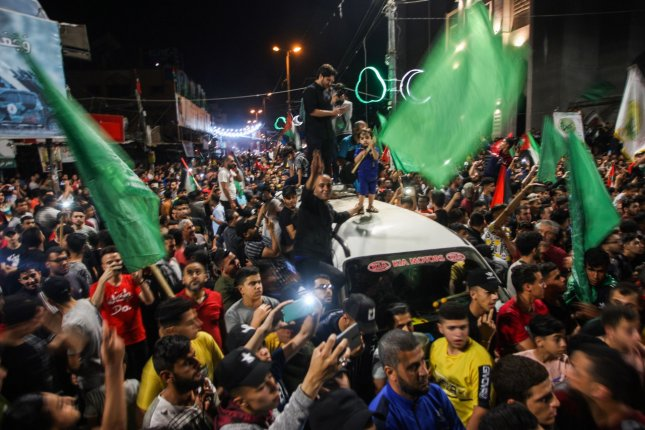 People celebrate in the streets following a ceasefire brokered by Egypt between Israel and the ruling Islamist movement Hamas, in Rafah, in the southern Gaza Strip on Friday. The cease fire follows 11 days of deadly fighting. Photo by Ismael Mohamad/UPI