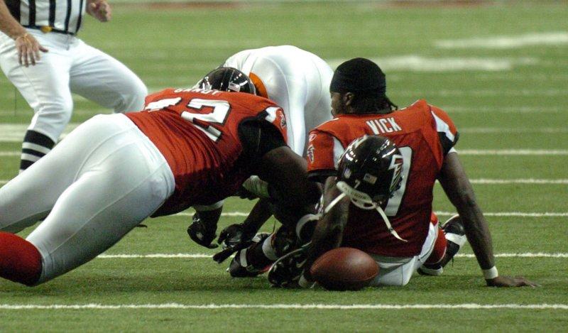 Atlanta's Wayne Gandy (L) goes for a fumble during a Nov., 12, 2006 game. (UPI Photo/John Dickerson)..