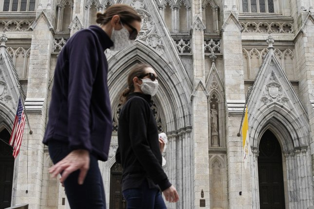Pedestrians wearing protective face masks walk by St. Patrick's Cathedral on Palm Sunday In New York City. Photo by John Angelillo/UPI