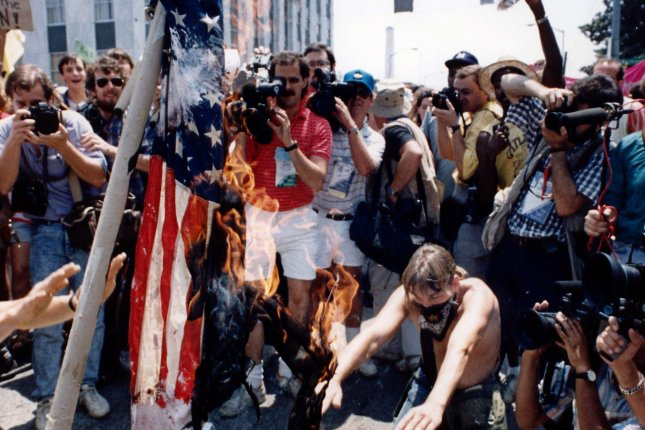 Anti-Ku Klux Klan demonstrators, protesting a scheduled march by the KKK on July 17, 1988, burn an American flag. On June 11, 1990, the U.S. Supreme Court struck down an anti-flag-burning law passed by Congress the year before. UPI File Photo