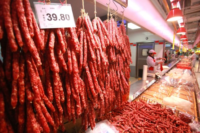 Crowded meat section in market in China. UPI/Stephen Shaver