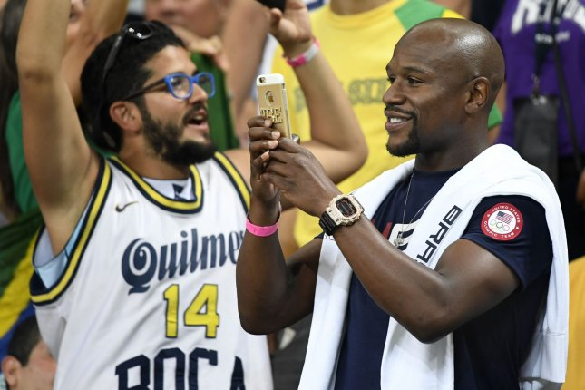 Former World Boxing Champion Floyd Mayweather (R) takes photos during a break in the action between the USA vs Argentina Men's Quarterfinal basketball game at the 2016 Rio Summer Olympics on August 17 in Rio de Janeiro, Brazil. File photo by Mike Theiler/UPI