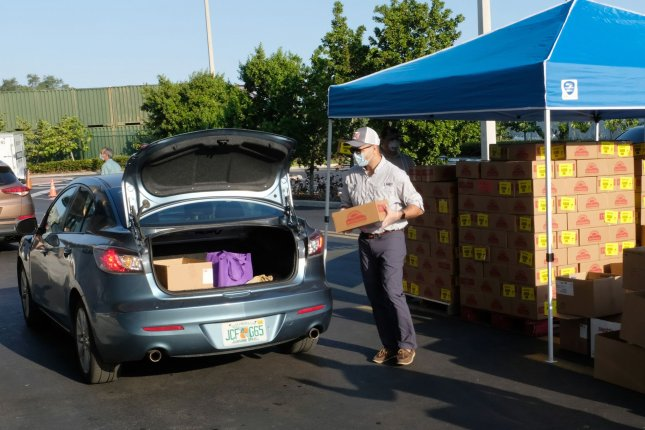 Vehicles line up Friday for a drive-through food distribution in Hialeah Gardens, Fla. By 8:30 a.m., almost 240 cars had passed through. Photo By Gary Rothstein/UPI